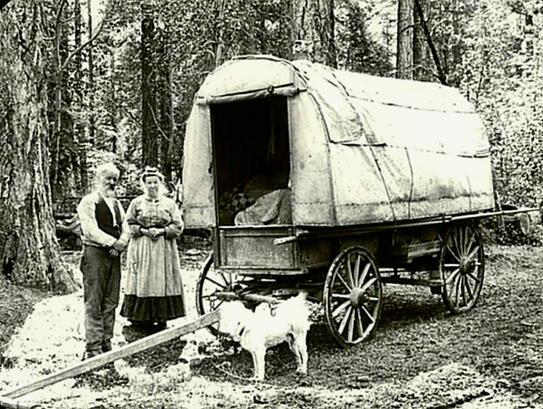 Oregon pioneers standing by their wagon
