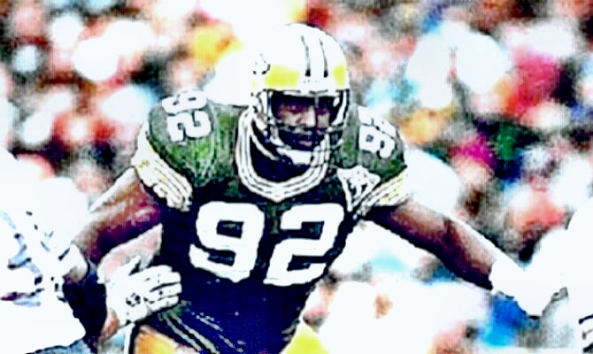 Reggie White as a Packer throwing blockers away